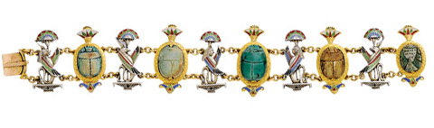 Egyptian Revival enamel and hard stone bracelet, with scarab carvings, lotus blossoms, and animal deities. Mounted in silver and 14-karat gold, circa 1920.