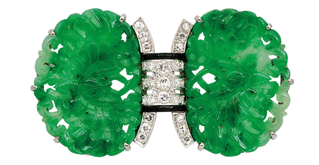 Platinum and 18-karat gold art deco brooch with jadeite plaques carved as a pair of butterflies amongst flowers, centring a diamond-set arch accented by black enamel.