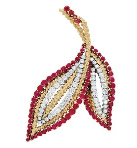 A claw-set diamond, ruby, and 18-karat gold leaf brooch by Van Cleef & Arpels.